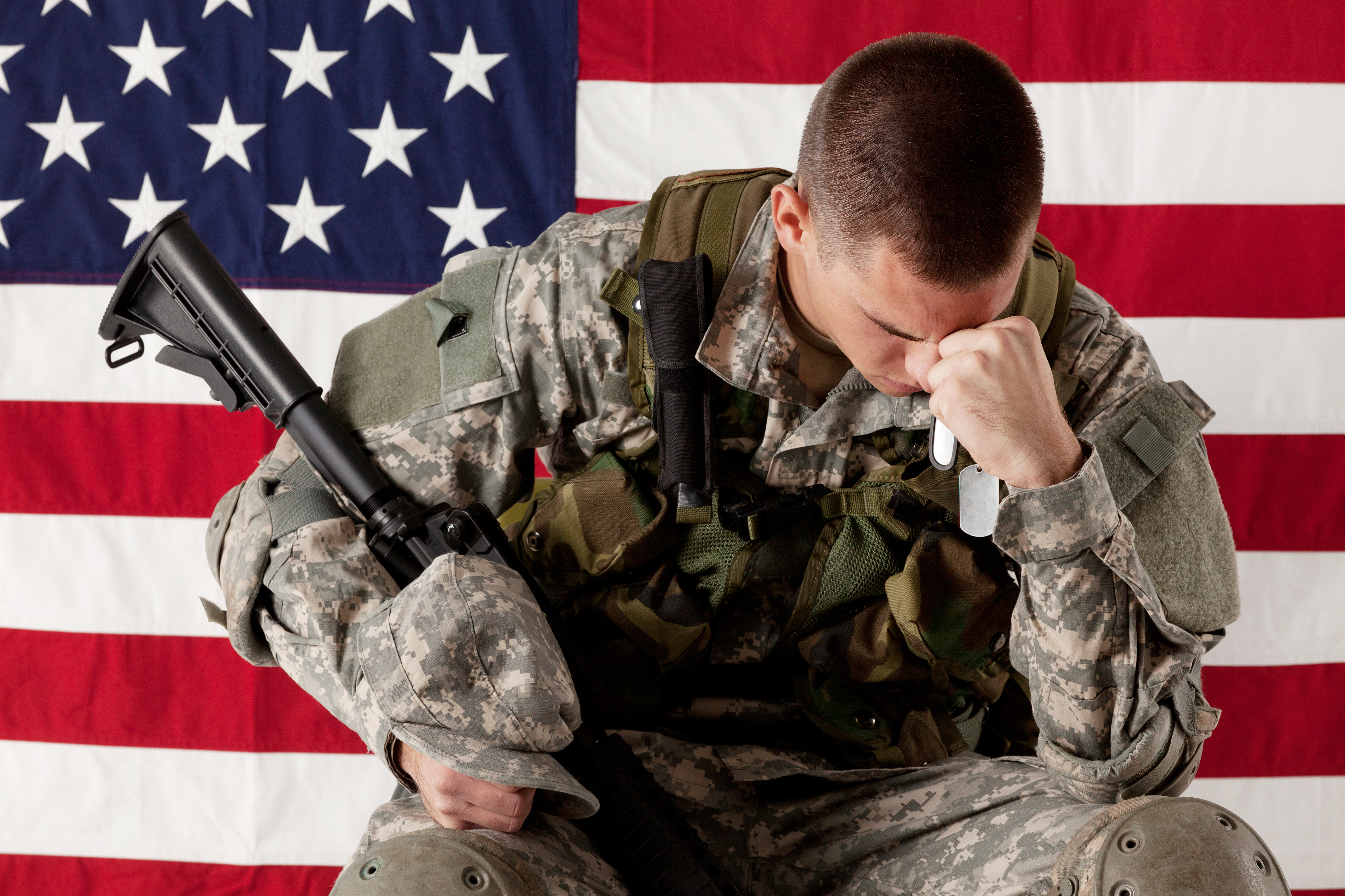Army man sitting in front of an American flag